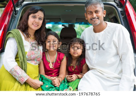 Happy Asian Indian family sitting in car, ready to summer vacation. - stock photo