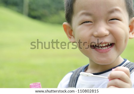 happy asian kid playing soap bubble ,candid