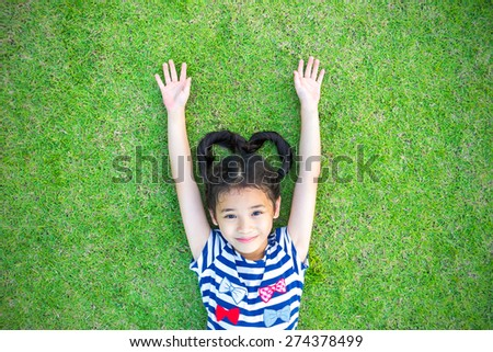 Happy Asian kid raising up two hands lying on lawn grass field: Smiling little girl with heart-shaped hair having freedom fun time on turf ground: Healthy child loves natural clean environment concept - stock photo