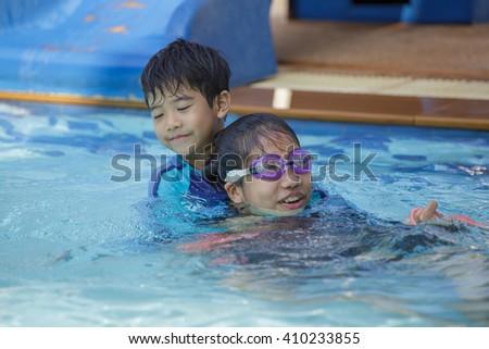 Happy Asian kids having fun at swimming pool - stock photo
