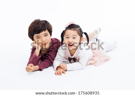 Happy Asian kids lying isolated on white background.