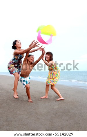 happy asian kids playing at the beach - stock photo