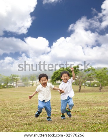 happy asian kids running on the grass - stock photo