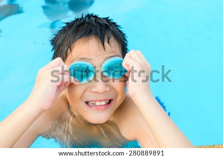happy asian little boy playing in the pool - stock photo