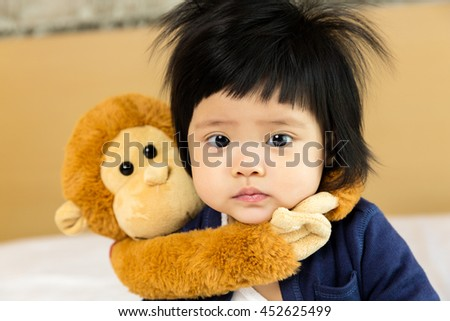 Happy asian little girl 7 month with playing with monkey doll