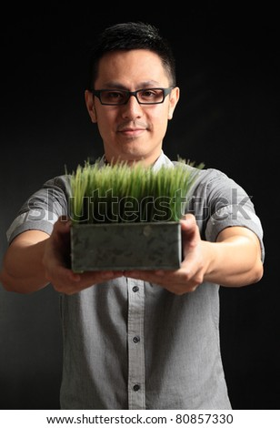 Happy Asian man holding plant in hands - stock photo