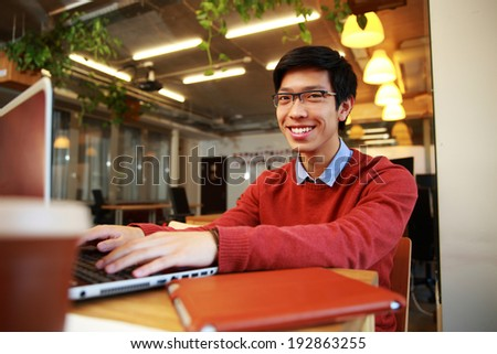 Happy asian man in glasses working on laptop in office - stock photo