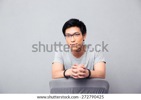 Happy asian man sitting on the chair and looking at camera over gray background