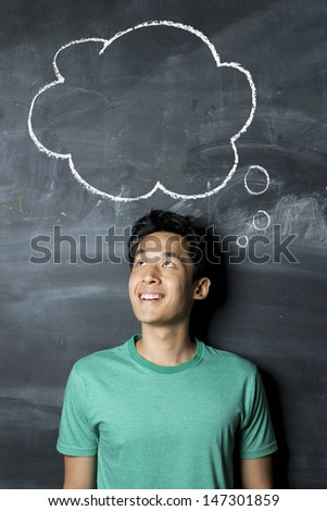 Happy Asian man standing under thought bubble hand drawn on a dark chalkboard. - stock photo