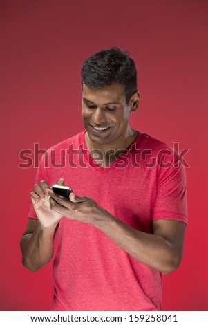 Happy Asian man talking on cell phone. Standing against red background.