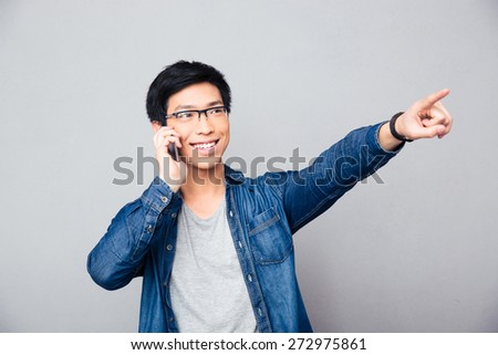 Happy asian man talking on the phone and showing finger away over gray background - stock photo