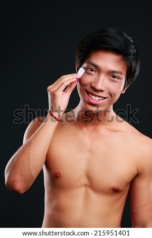 Happy asian man wipes his face with cotton pad on black background - stock photo