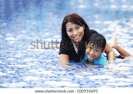 Happy Asian mother and son posing at swimming pool - stock photo
