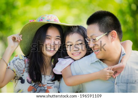 Happy asian mother, father and daughter playing in the park - stock photo
