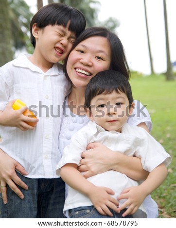 happy asian mother having outdoor fun with sons - stock photo