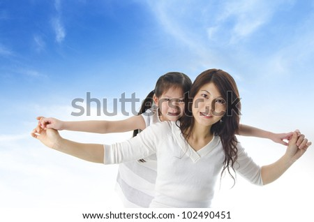 Happy Asian mother piggyback ride daughter over blue sky - stock photo