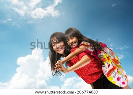 Happy asian mother piggyback ride her daughter over blue sky - stock photo