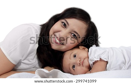 Happy Asian mother with her baby daughter lying together on bed, isolated on white background - stock photo