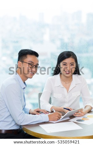 Happy Asian people using tablet in office