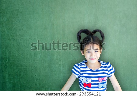 Happy Asian school child girl with heart shaped hair on green color chalkboard background : Smiling lovely female little kid with empty copy space on writable cement concrete backdrop for adding text  - stock photo