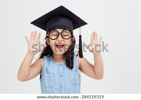 Happy Asian school kid graduate in graduation cap - stock photo