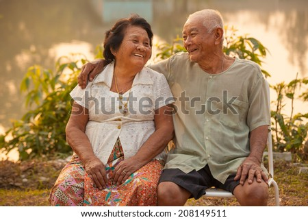 Happy Asian Senior couple sitting outdoors on sunset - stock photo