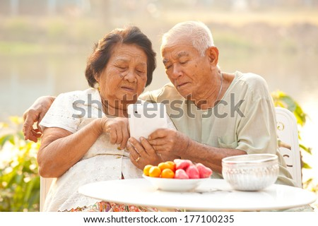 Happy asian senior couple using the tablet on outdoor background