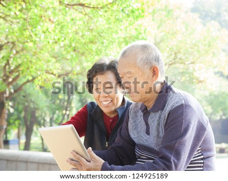 happy asian  Senior couple with tablet pc - stock photo