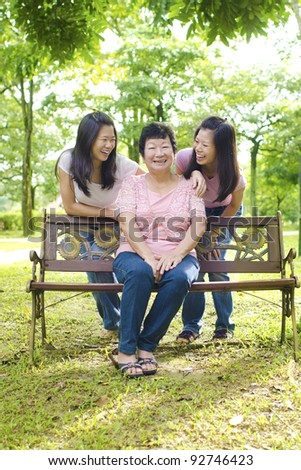 Happy Asian senior mother with her daughters - stock photo
