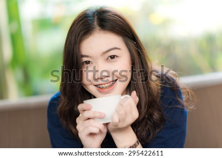 Happy asian smiling female student drinking coffee, Close up