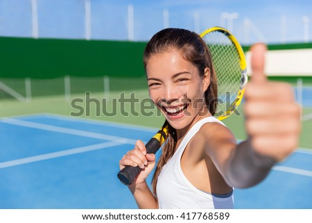 Happy Asian tennis player girl showing thumbs up hand sign after game fun holding racket on outdoor blue hard court for summer class. Sports ethnic young woman smiling of satisfaction. - stock photo