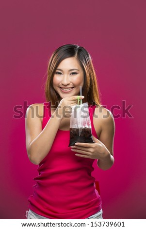 Happy Asian Woman drinking an iced coffee from a bag on a colorful background. Young and fresh Asian female model an pink background.