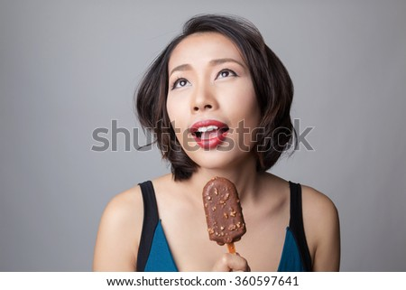 Happy asian woman eating ice cream, looking up to copy space. - stock photo