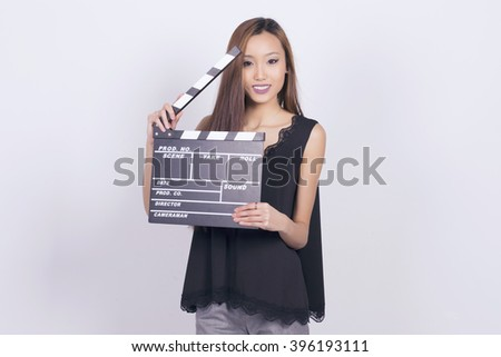 Happy asian woman holding a cinema clapper board, smiling over a grey background. Concept: Let the show begin!.