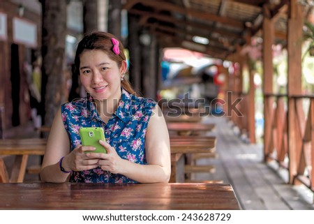 Happy Asian woman is playing her mobile phone to communication with another people
