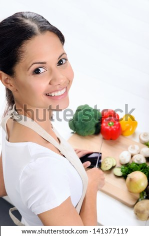 Happy asian woman looks over her shoulder while slicing and preparing food in the kitchen - stock photo