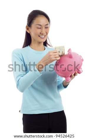 Happy Asian woman putting money in piggy bank isolated over white background