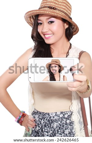 Happy asian woman taking a selfie using her smartphone, isolated on white background - stock photo