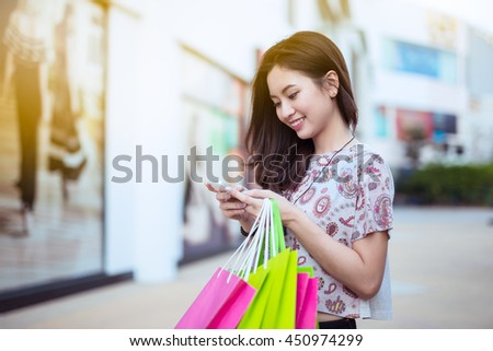 Happy asian woman using cell phone at a shopping center,high key.