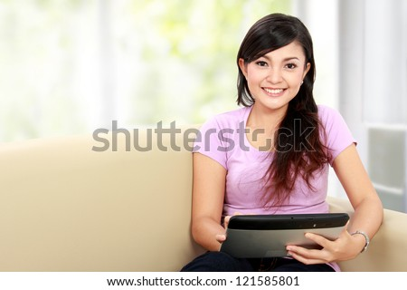 happy asian woman using tablet pc while sitting on the couch - stock photo