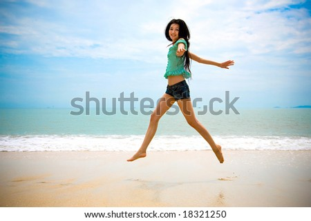 happy asian woman walking in the air at the beach on sunny day - stock photo