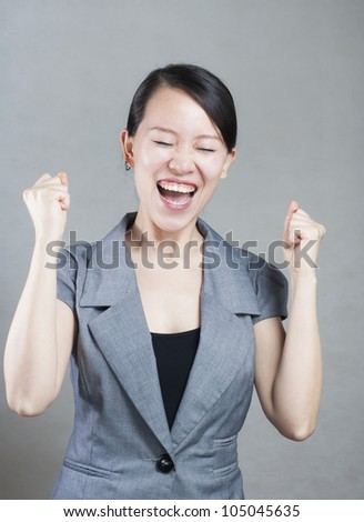 Happy Asian woman with her arms in the air cheering