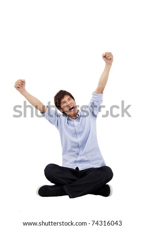 Happy Asian young man sitting and looking up - stock photo