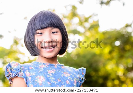 Happy Asiangirl relaxing in the park outdoor with nature light and flare. - stock photo