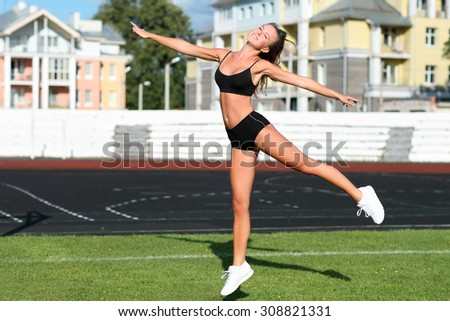 Happy athletic girl jumping in outdoors on a summer day