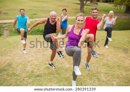 Happy athletic group training on a sunny day - stock photo