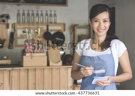 Happy attractive asian female waiter in apron writing order and looking at camera - stock photo