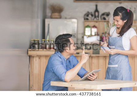 Happy attractive asian female waiter in apron writing order of a male customer - stock photo