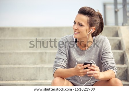 Happy attractive athlete sitting and listening to mp3 music while resting
