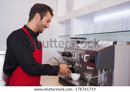 Happy attractive barista making cup of coffee in a cafe